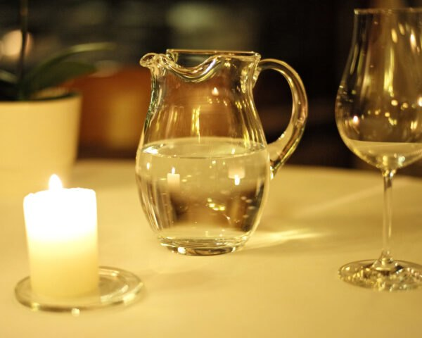 glass pitcher of water on table near a candle