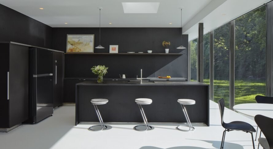 all-black kitchen in home with glass walls