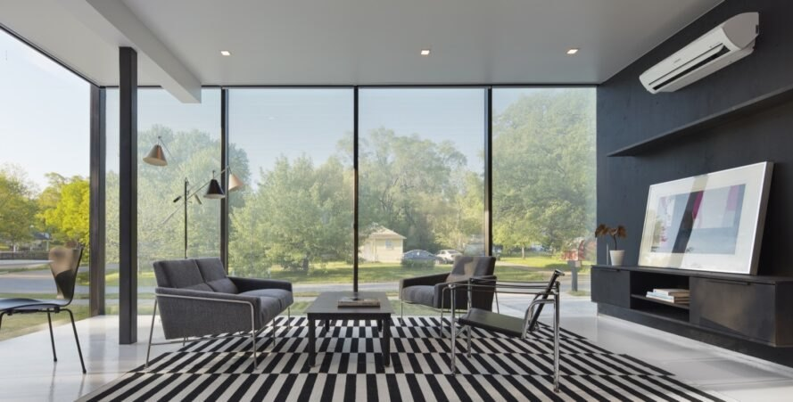 black and white living room in home with glass walls