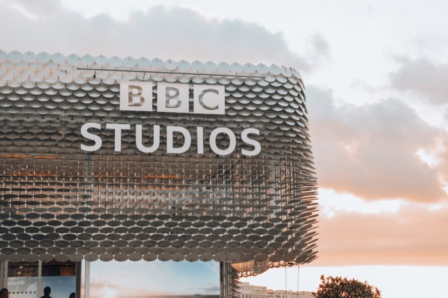 "aluminum pavilion with sign that reads ""BBC Studios"" at sunset"