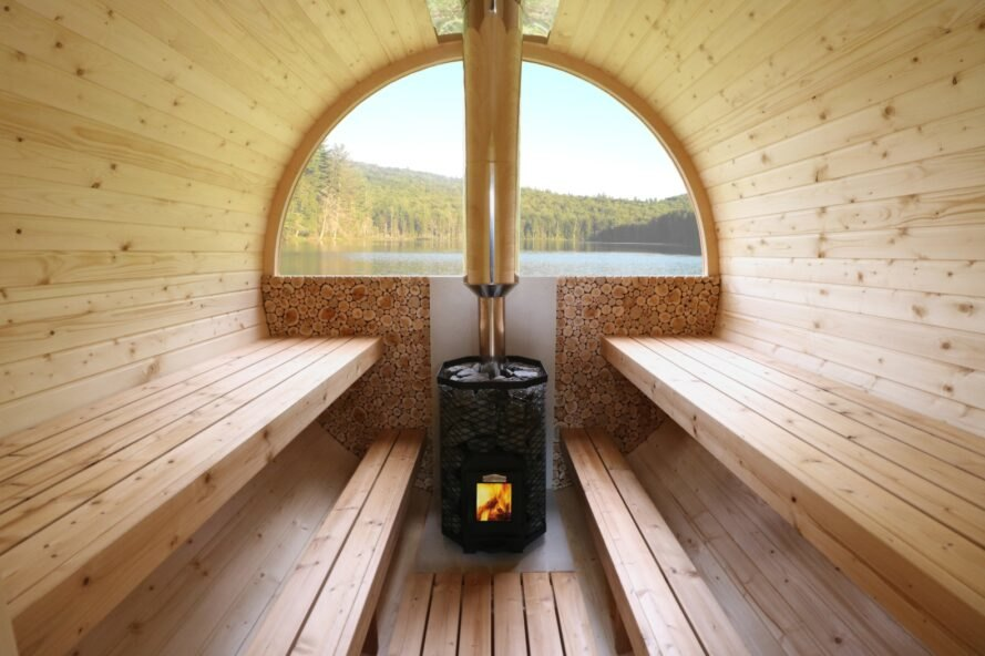 interior of oval-shaped wooden sauna with wood-burning stove