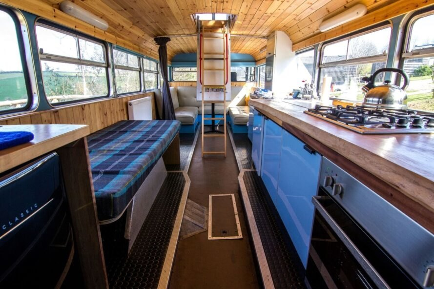 bus interior with long sofa and small blue kitchen
