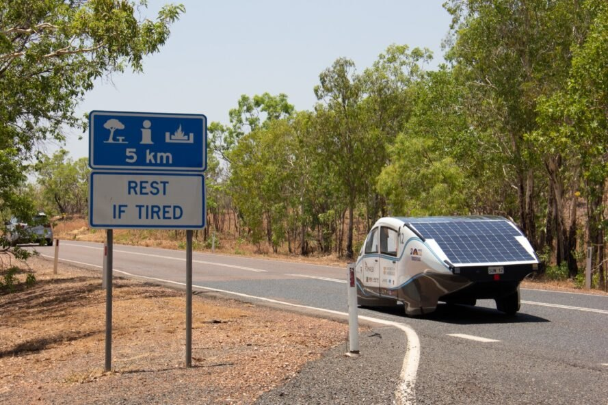 white car with solar panels driving on a road