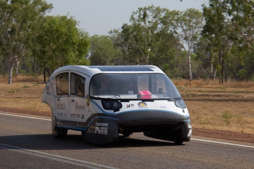 white solar-powered electric car driving down a road