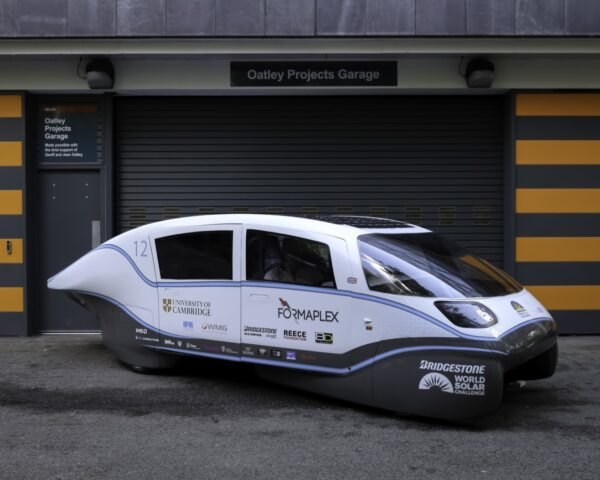 white solar-powered car in front of gray and orange building