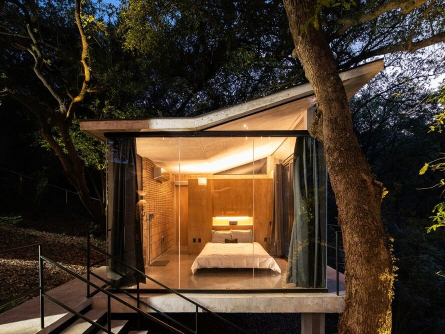 small pavilion with glass walls revealing a bed inside