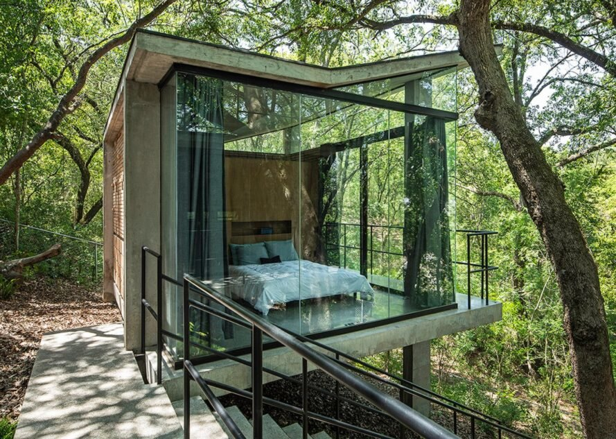 home with glass walls revealing a bed inside