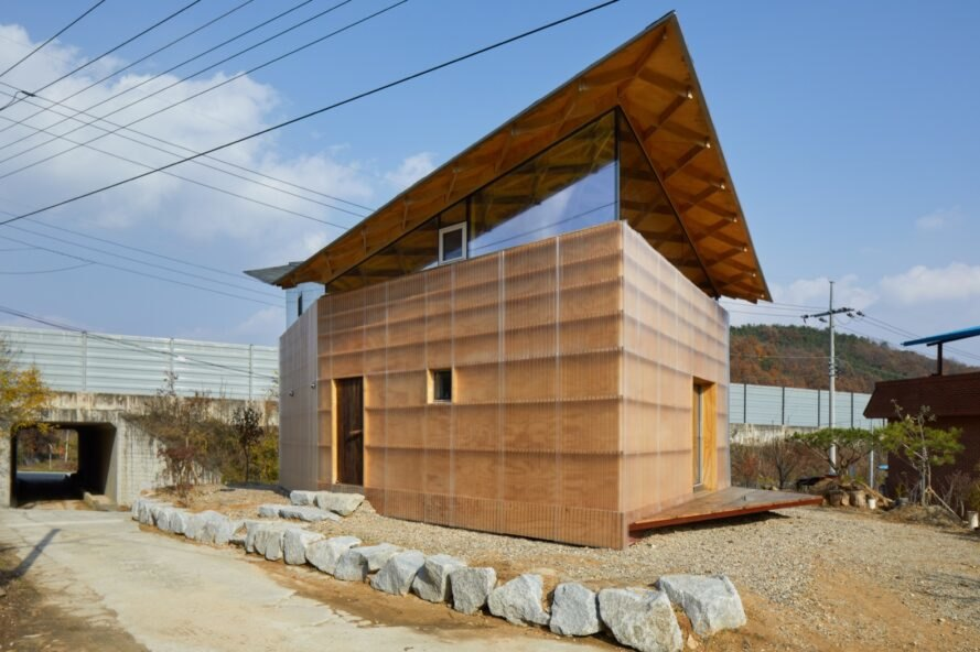 tan and glass home with butterfly roof