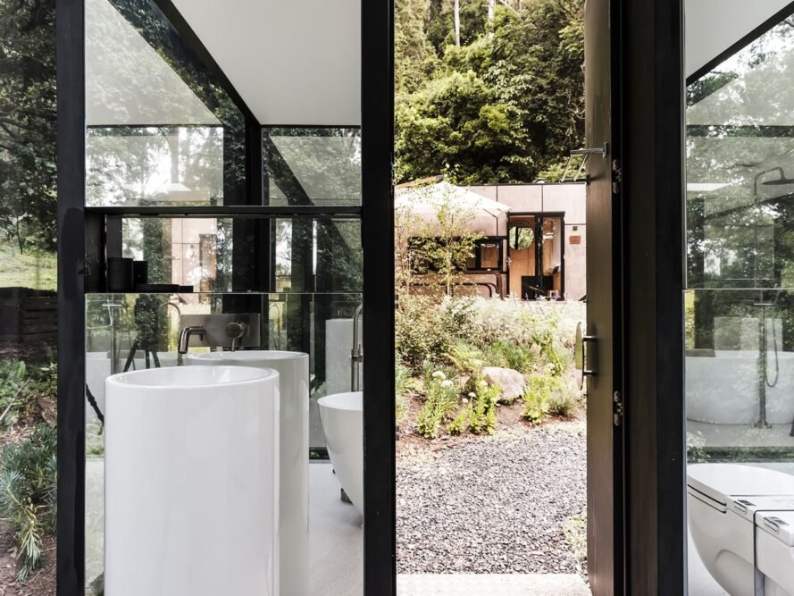 sink against a glass wall and beside a door opening to the forest