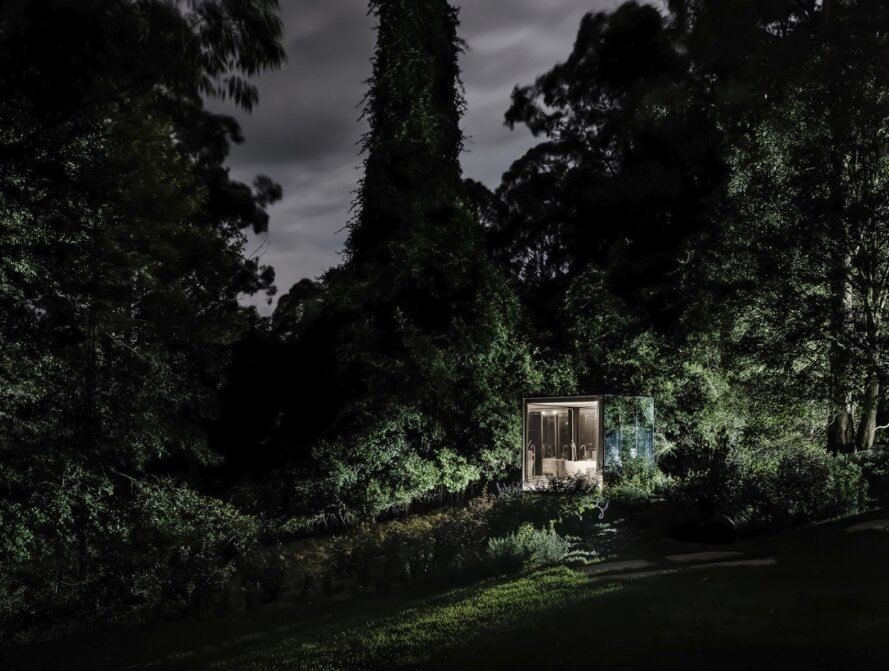 small mirrored building lit up at night in a forest
