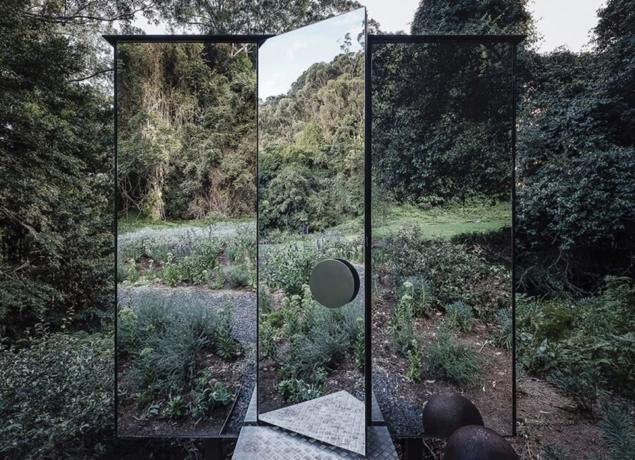 mirrored door opening to a mirrored building in a forest