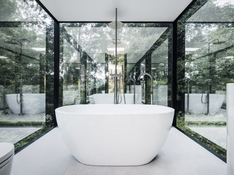 white free-standing tub in small room with glass walls