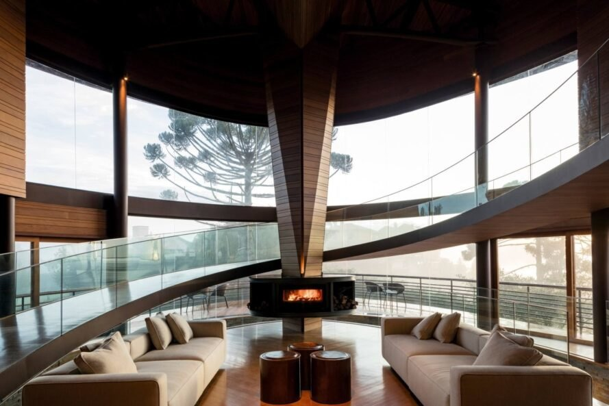white sofas near a fireplace in room with curved glass walls