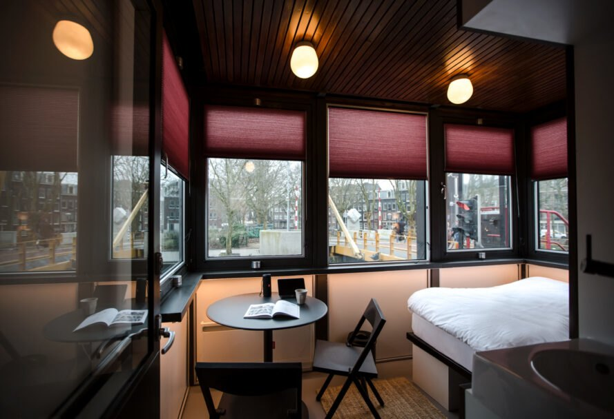 double bed and dinette set in small hotel room with many windows