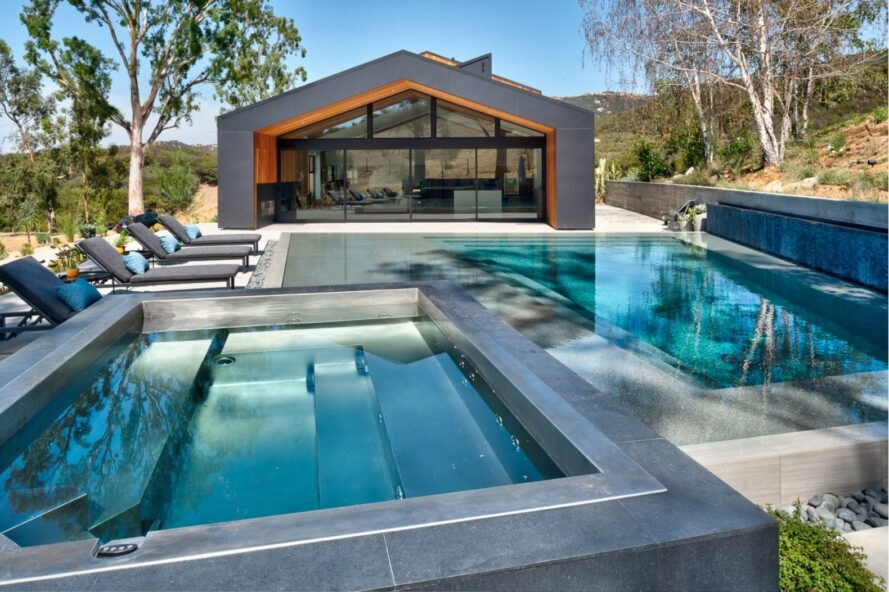 pool behind dark metal and cedar home with gabled roof