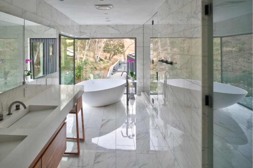 marble bathroom with freestanding tub next to a full-height window