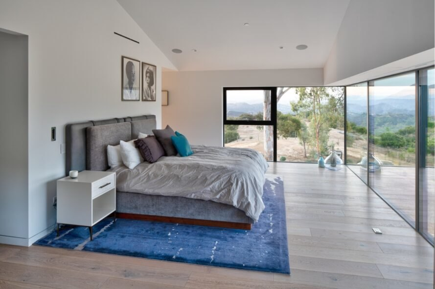 gray bed and blue rug in large white bedroom with some walls made of glass