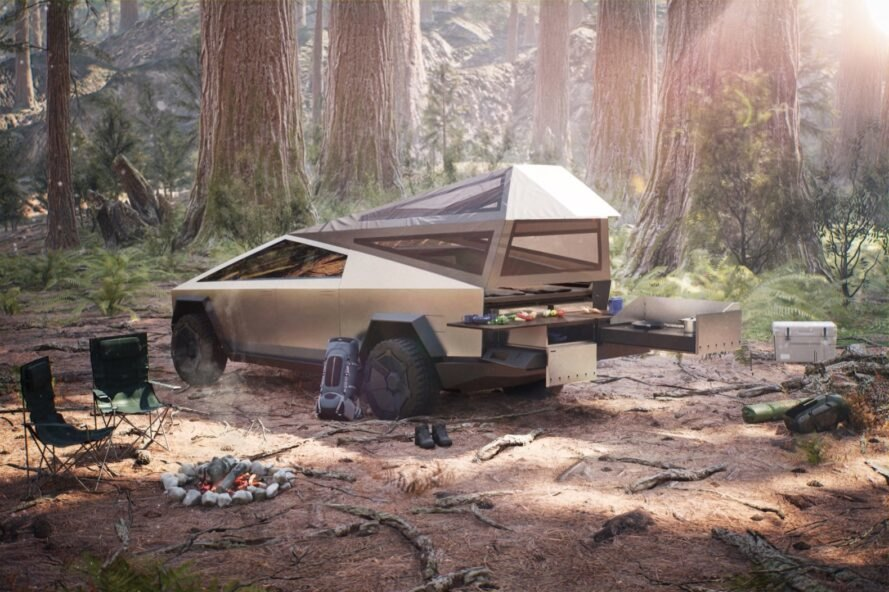 gray angular pickup truck with camping gear in forest