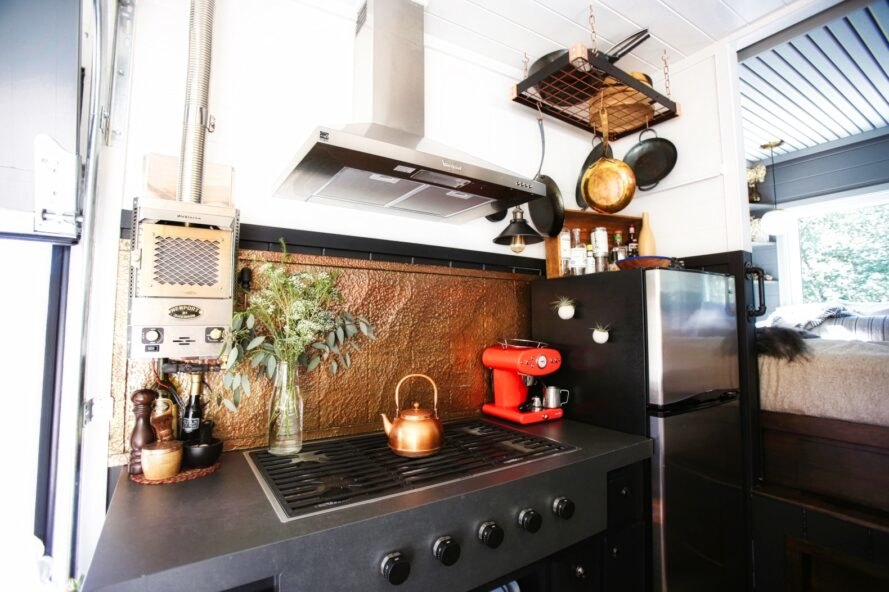 kitchen stovetop with copper backsplash