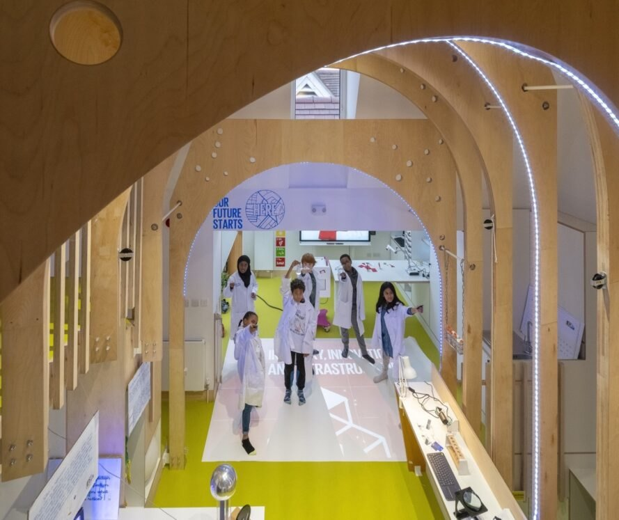 students wearing lab coats inside lab with yellow floors and plywood arches