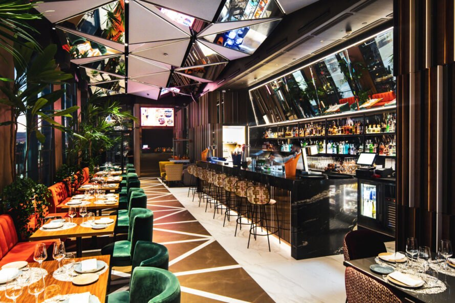 restaurant with geometric floors and ceilings and a long, dark bar area
