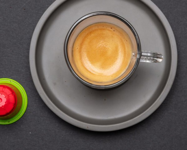two red and green compostable coffee pods next to a cup of espresso
