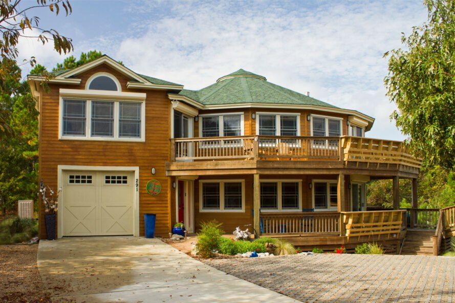 round wood home with upper and lower level decks