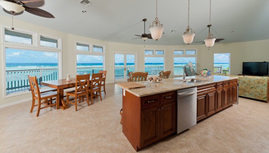 wood kitchen island and wood dining table facing curved wall of windows with ocean views