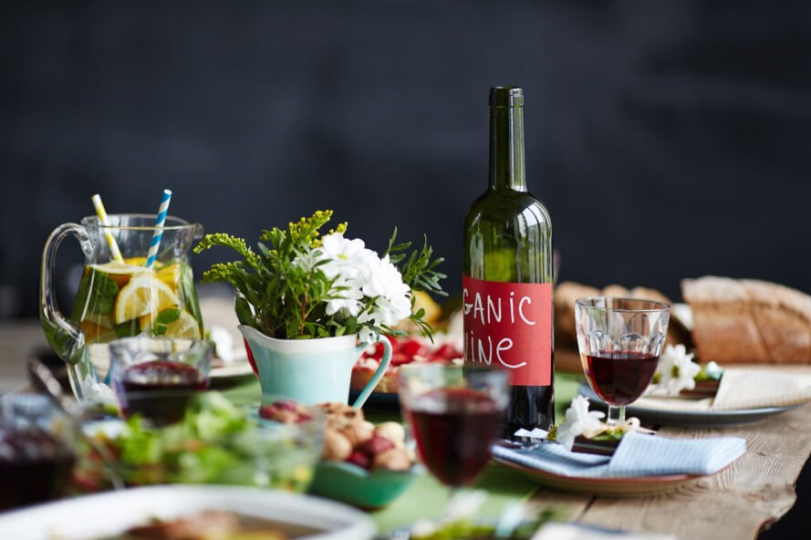 "wine bottle with red ""Organic Wine"" label on table with food"