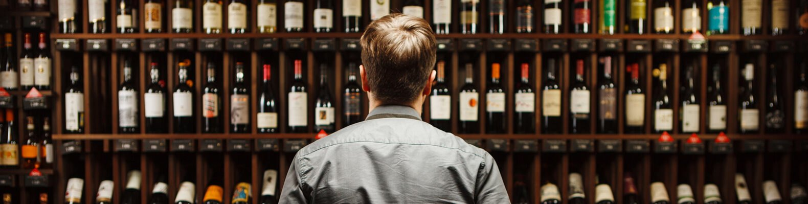 person standing in front of wall filled with wine bottles