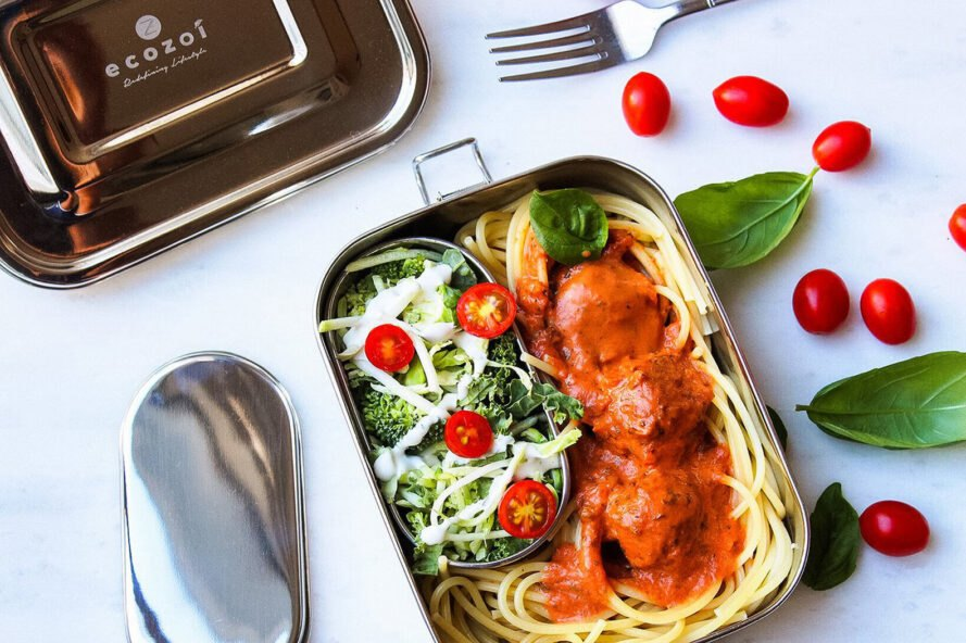 spaghetti and meatballs and salad in a steel lunch box