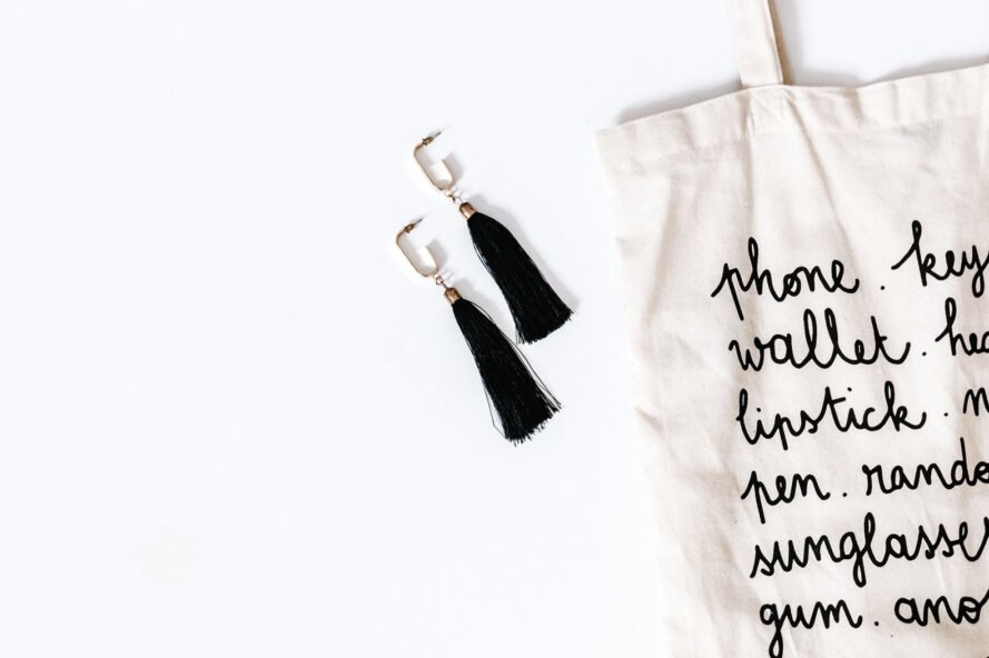 black and white reusable tote next to black tassel earrings
