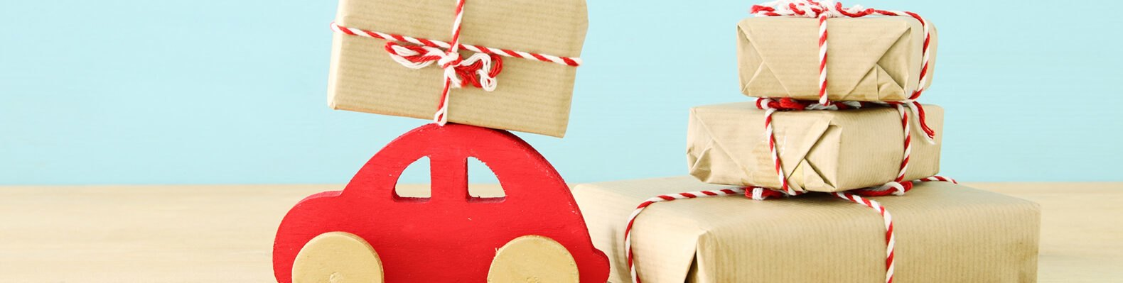 red wood car near butcher paper-wrapped gifts