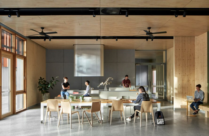 room with wood ceilings, a glass wall and several study tables