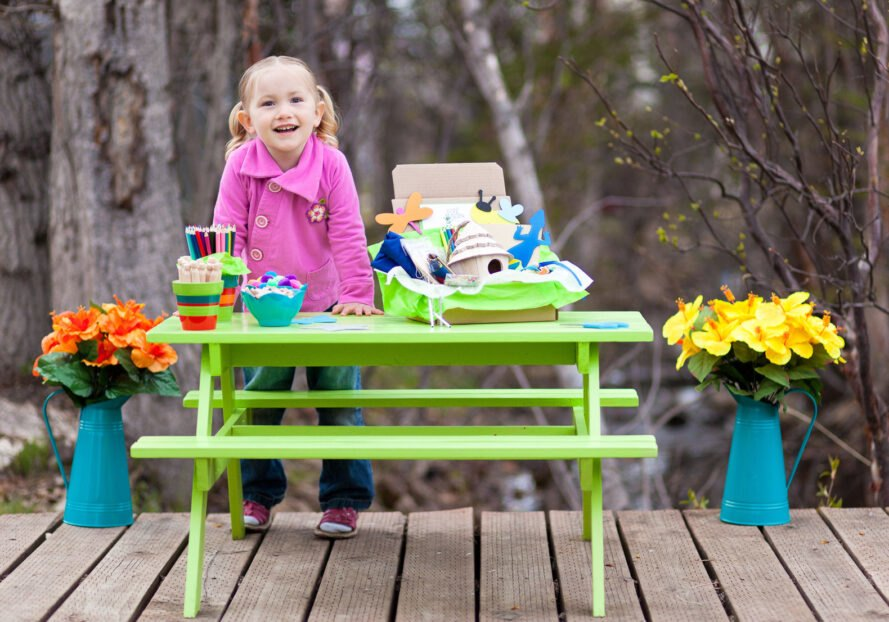 child playing with science craft kit outside at green picnic table