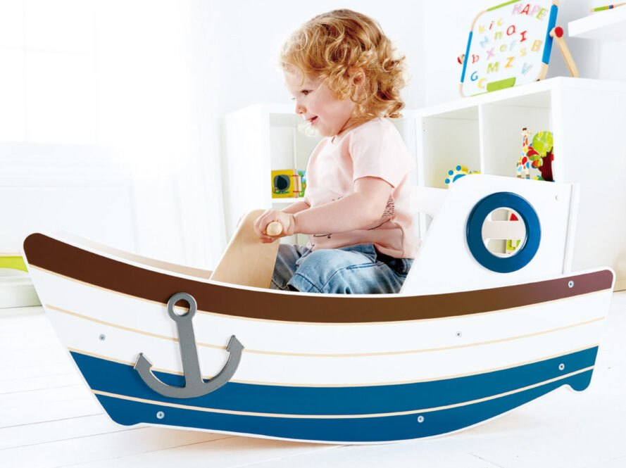 child playing in a small wood boat
