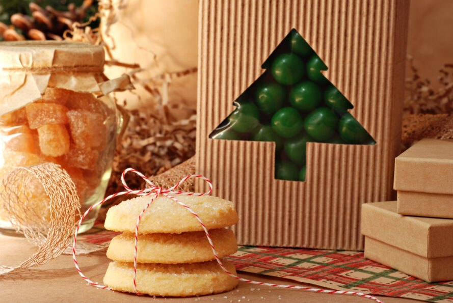 green candy in cardboard package, orange candy in glass jar and sugar cookies tied in string