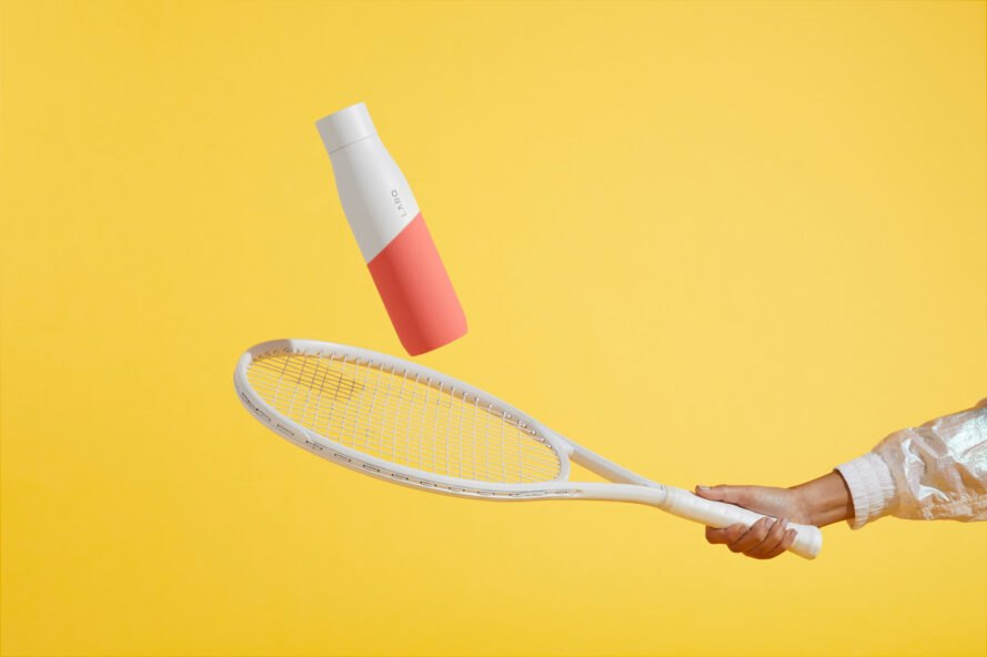 person hitting white and coral water bottle with a white tennis racket
