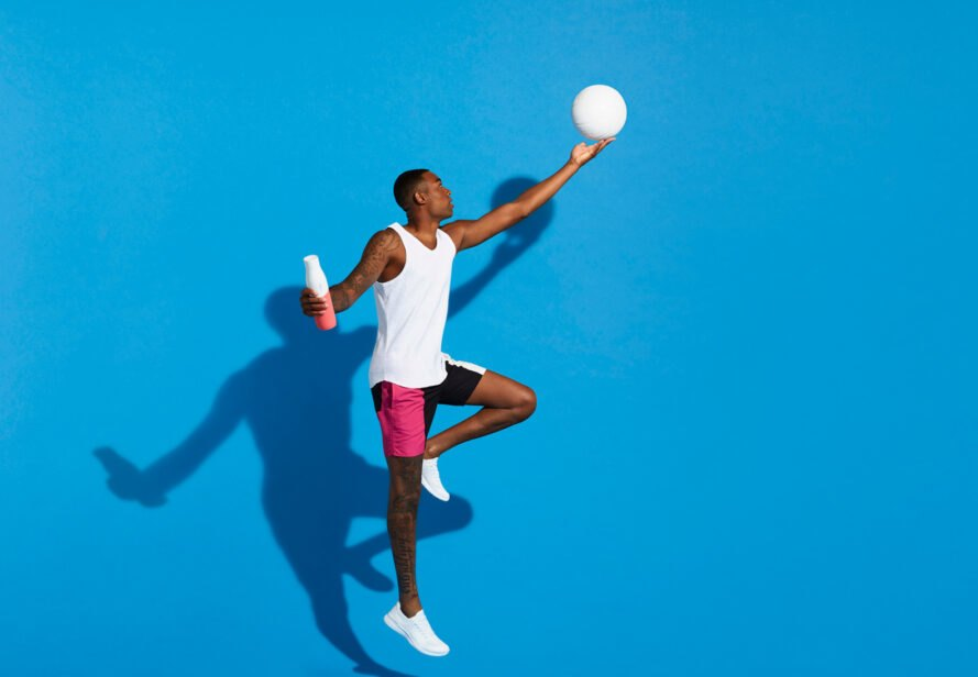 person holding white and coral water bottle with one hand and hitting a ball with another hand