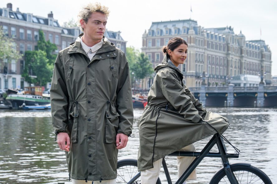 man and woman wearing dark green parka coats in a city
