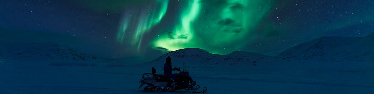 Person on electric snowmobile looking at northern lights