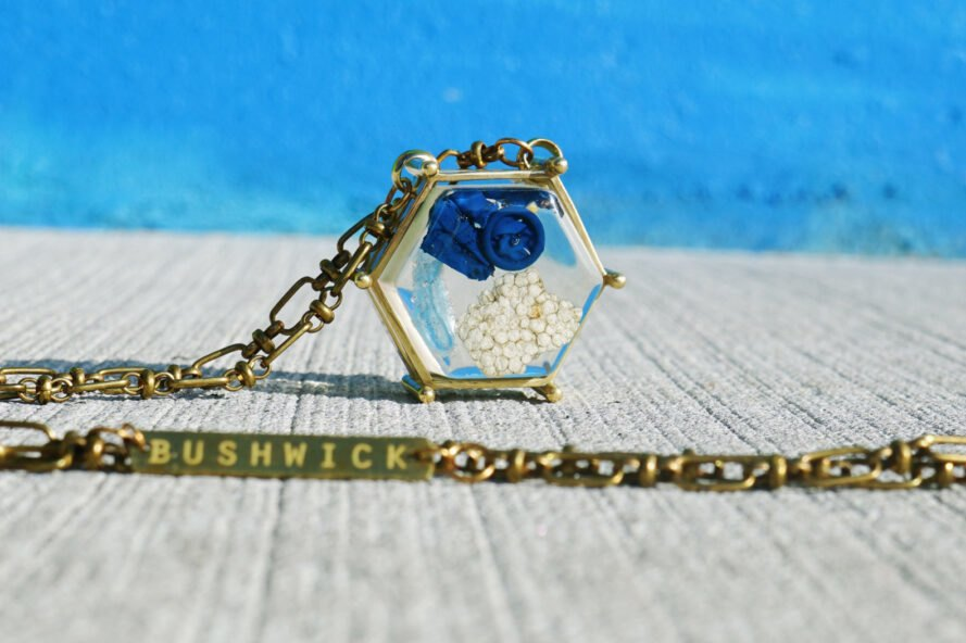 blue balloon and chunk of Styrofoam inside a gold pendant