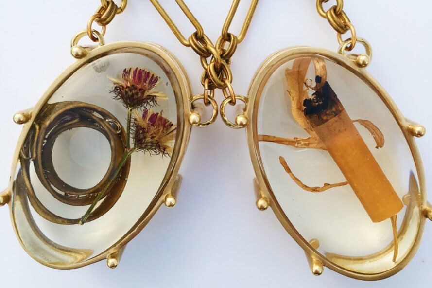 two gold pendants, one filled with dead flowers and one filled with a cigarette butt