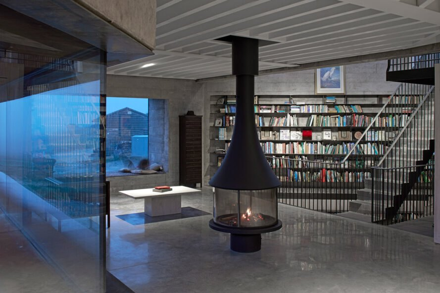 black fireplace in room with floor-to-ceiling bookshelves