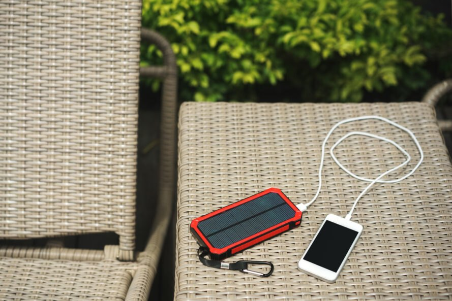 phone plugged in to solar-powered charger outside on patio furniture
