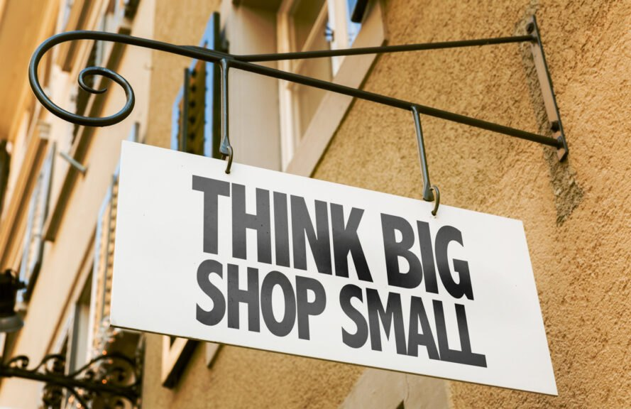 "shop sign that reads, ""Think Big, Shop Small"" on brick building"