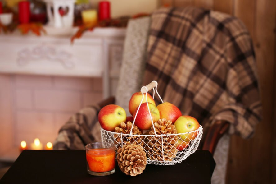 end table with basket of apples and pinecones