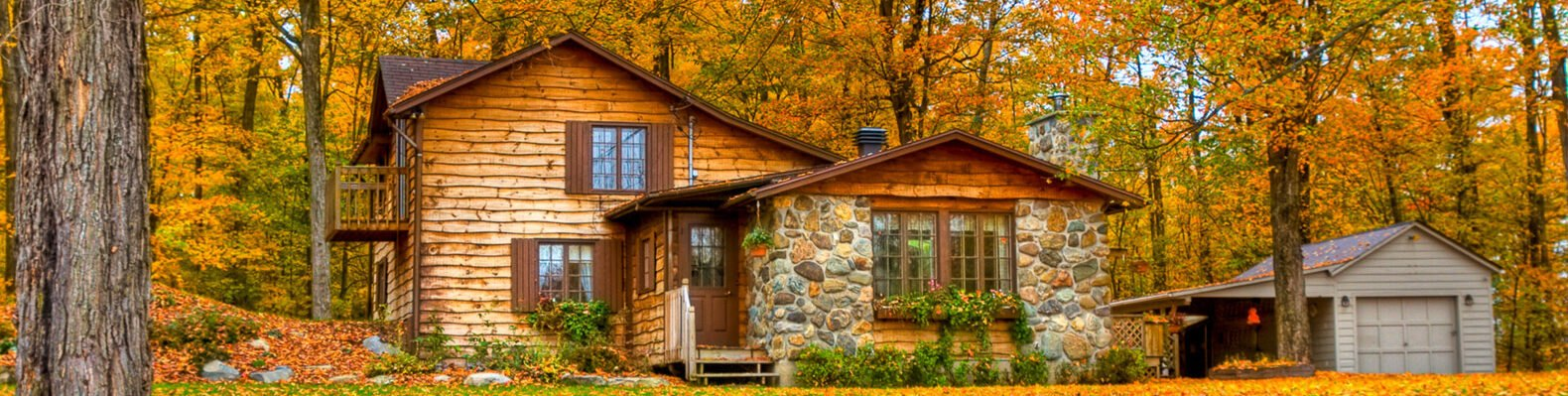 wood and stone home in a forest in the fall
