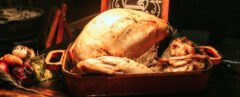 turkey in a roasting pan on a wood table