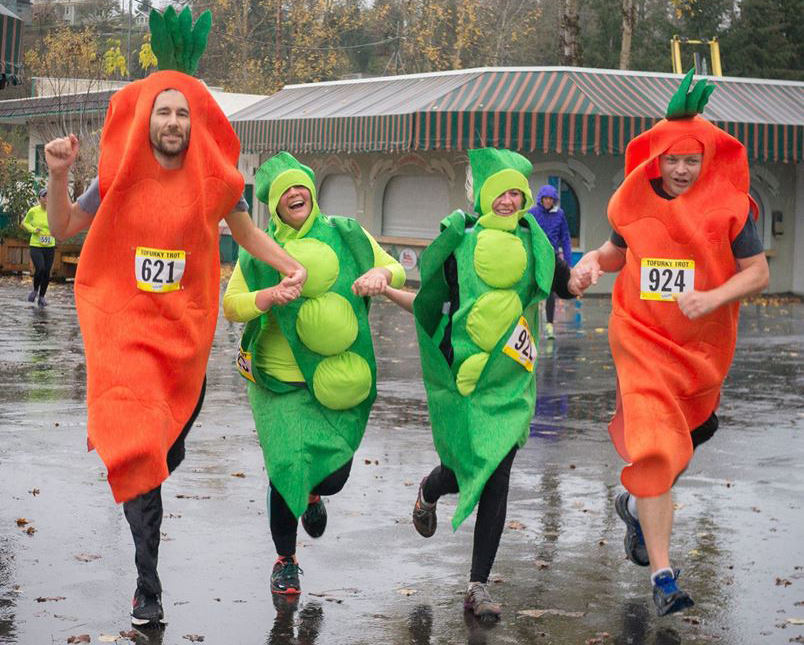 people in pea and carrot costumes running a race